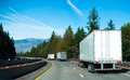 Convoy Semi trucks dry van trailers on winding highway interstate I-5 back view Royalty Free Stock Photo
