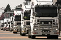 Convoy of white heavy trucks Stock Images