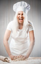Cook angry and stressed out woman kneading dough Stock Photo