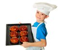 Cook boy six years old holding baking tray with fresh buns in the hand isolated on white Royalty Free Stock Image