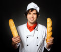Cook with bread holds on a black background Royalty Free Stock Photo
