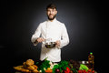 Cook chef with vegetables splah and black dark background. Food musical harmony. Chef juggling with vegetables and other food in t Royalty Free Stock Photo