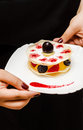 Cook with delicate dessert holding berries Stock Images