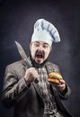 Cook with hamburger and knife screaming in hat holding at dark background Stock Photos