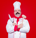 Cook holding knife and beater strict Royalty Free Stock Photos