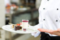 Cook pastry chef in hotel or restaurant kitchen the female cooking she is finishing a sweet dessert Stock Images