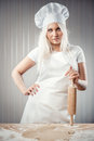Cook with rolling pin woman holding wearing uniform posing indoors Royalty Free Stock Images