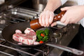 Cook seasoning meat with pepper from a mill Stock Photos