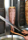 Cook slicing turkish lamb doner kebab with a sharp sword like knife and holding wooden spoon in kusadasi turkey Stock Image