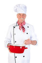 Cook stirring in the pan is with wooden spoon and red Stock Image