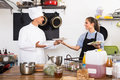 Cook and waitress at cafe's kitchen Royalty Free Stock Photo