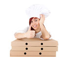 Cook woman with thumb up leaning on boxes of pizza Stock Images