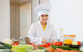 Cook works with vegetables at commercial kitchen Royalty Free Stock Photo