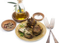 Cooked artichokes a plate with served with olive oil pepper and salt isolated on white background Royalty Free Stock Images