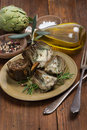 Cooked artichokes a plate with served with olive oil pepper and salt on the wooden table Stock Photos
