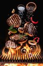 Cooked beef steaks with vegetables and spices fly over the blazing grill barbecue fire Royalty Free Stock Photo