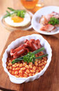 Cooked breakfast or brunch english of baked beans sausages fried egg and bacon Royalty Free Stock Photos