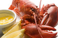 Cooked lobster with butter and lemon wedges Royalty Free Stock Photo