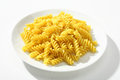 Cooked macaroni a portion of served without sauce on white plate against a white backdrop Royalty Free Stock Photo