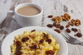 Cooked millet groats on white plate and cup of coffee with milk, healthy food and nutrition