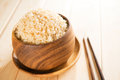 Cooked organic basmati brown rice with chopsticks in wooden bowl on dining table Stock Images