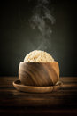 Cooked organic basmati brown rice with steam in wooden bowl hot smoke on dining table low light setting Royalty Free Stock Image