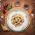 Cooked paella with seafood dish on a chopping board with bread seasoned with herbs and tomatoes  a fork on rustic wooden backg Royalty Free Stock Photo