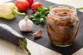 Cooked stewed eggplants jar canning raw vegetables garlic parsley tomatoes pepper wooden table Royalty Free Stock Photos