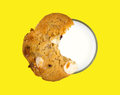 Cookie atop glass of skim milk top view a on the rim a filled with on a bright yellow background Stock Photos
