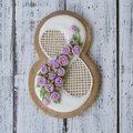 Cookie covered with glaze made in a form of number eight with sring flowers on white wooden background. Ginger biscuits
