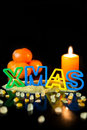 Cookie cutter building the word Xmas, tangerines and candle, bla Royalty Free Stock Photo