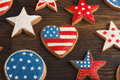 Cookies with american patriotic colors different shapes on the wooden background Royalty Free Stock Image
