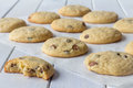 Cookies on baking paper with one partly eaten homemade chocolate chip white wooden table Royalty Free Stock Photo