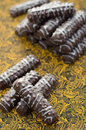 Cookies in chocolate cookie sticks on cardboard with yellow openwork pattern Stock Photos