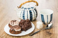 Cookies with chocolate and nuts, striped teapot, cup, lumpy sugar