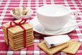 Cookies cup with hot water and tea bag tied red ribbon on a red tablecloth Stock Photos