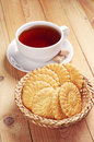 Cookies and cup of tea in wicker bowl on wooden table Stock Photography