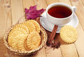 Cookies and cup of tea in wicker bowl on wooden table Stock Photo