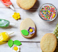 Cookies with decorations tools – icing, marzipan flower, nonpareil Royalty Free Stock Photo