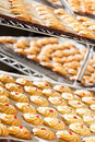Cookies by the dozen a variety of decorated biscuits cooling off on baking trays in bakery Stock Photography