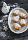 Cookies madeleines with powdered sugar on the oval plate, ceramic Santa Claus and Christmas decorations Royalty Free Stock Photo