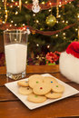 Cookies and milk for santa plate of shortbread with a glass of hat in front of the christmas tree Royalty Free Stock Photos