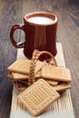 Cookies and mug of milk in wicker basket on wooden table Stock Images