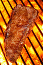 Cooking a beef steak on a fire hot barbecue grill Stock Photography