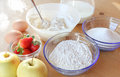 Cooking cakes bowls with sugar cream and flour and two fresh eggs with fresh strawberries and apples on a table outside Stock Photography