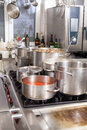 Cooking in a commercial kitchen with large stainless steel pots filled with stew and vegetables on central gas hob Stock Images