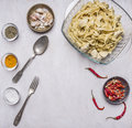 Cooking concept ready-made pasta with turkey in cream sauce with garlic, red chili peppers fork spoon spices in glass bowls on Royalty Free Stock Photo