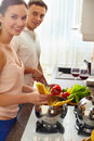 Cooking couple portrait of amorous spaghetti and salad in the kitchen Stock Image
