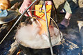 Cooking fish soup in the stowed bowler over campfire Royalty Free Stock Photo