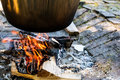 Cooking food on fire. Cooking outdoors in cast-iron cauldron. Royalty Free Stock Photo